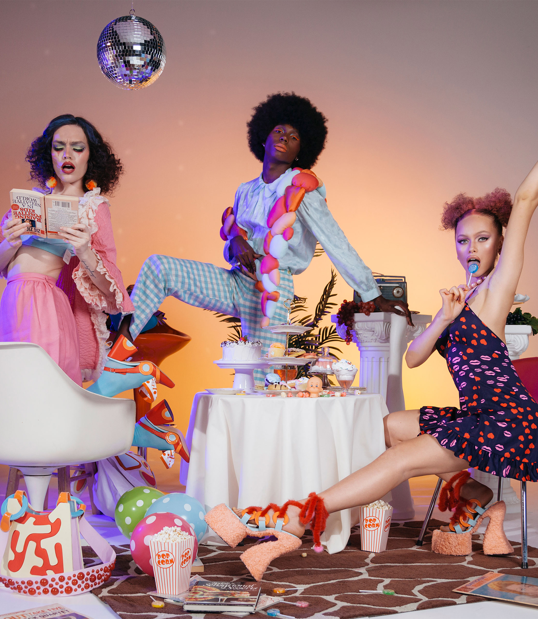 Models posing at a party with cakes and a disco ball